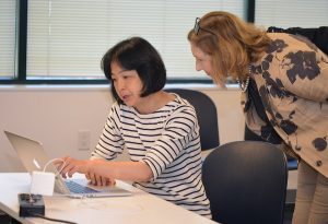 female instructor helping female student at her desk