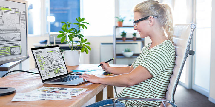 Female learner sitting at a desk viewing UX/UI concepts on a laptop