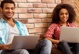 two students sitting with the backs on a brick wall smiling with their laptops