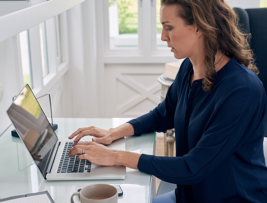 woman in her house typing on a macbook
